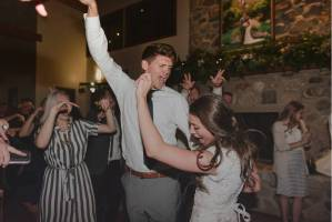 bride and groom dancing with hands in the air on dance floor at wedding