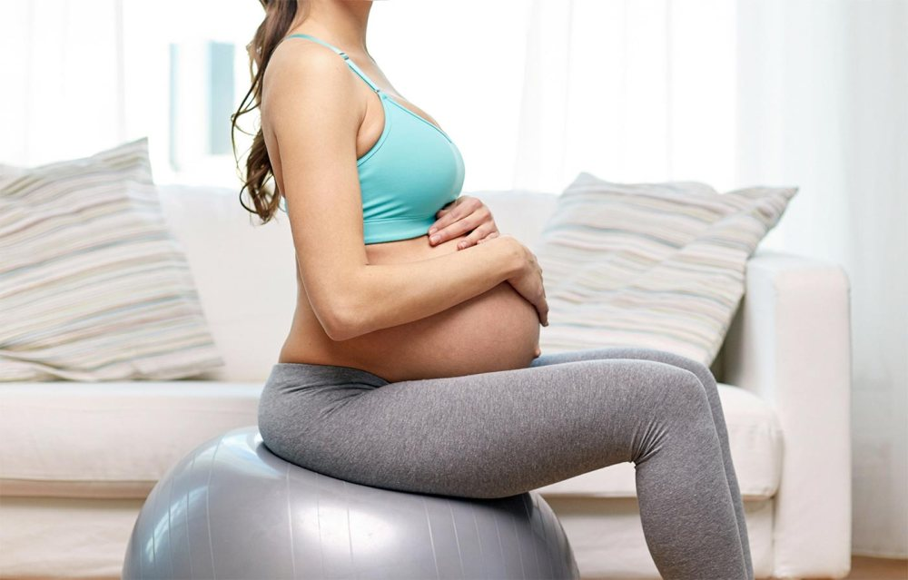 medium resolution of twin pregnant mom holding her belly sitting on a yoga ball