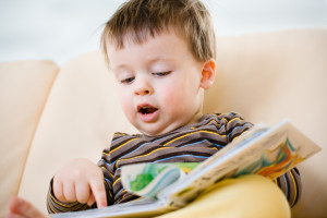 Cute little boy reading book on sofa