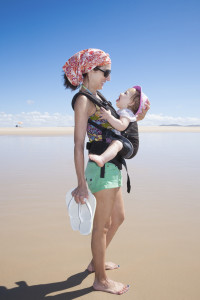 mother with headscarf green shorts carrying her one year baby with pink hat in front rucksack walking at a beach
