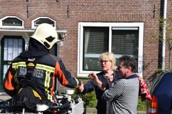 Brandweer haalt kat uit dakgoot onder toeziend oog van publiek, Formosastraat in Leiden
