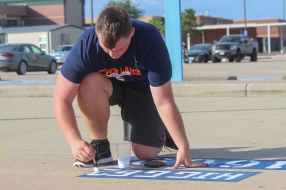 Excitedly painting his jersey number and nickname onto the parking spot, senior Preston Higginbottom adds the finishing touches to his masterpiece. Higginbottom served as the starting varsity guard on the boys football team, participated in track and field, and took part in FFA.
