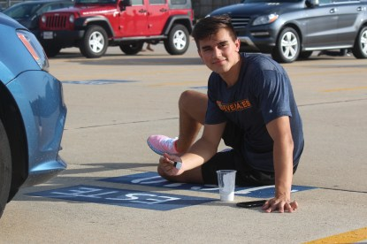 """Senior Esteban Schrick paints a simple design on his senior spot. His nickname """"Este"""" was clearly printed on his spot so he could distinguish it from his teammates' spots, since they all parked together in a row."""