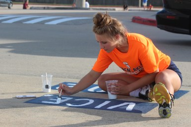 """Finishing off her friend's parking spot masterpiece, senior JoAnna Vanvalkenburgh writes the word """"VICE"""" with her friend's jersey number 8. Vanvalkenburgh parked alongside her volleyball teammates in the backlot."""