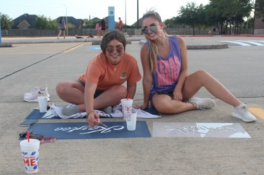 Seniors Kaylee Mahdavi and Pige Heilman sit together and trace over a stencil for Mahdavi's senior spot. Many students opted to use stencils because of how easy they were to paint over.