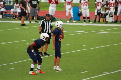 Sophomore Adam Peters and junior Jalen Mosely get ready to run the next play of the game. After the ball snaps the quarterback starts the play.