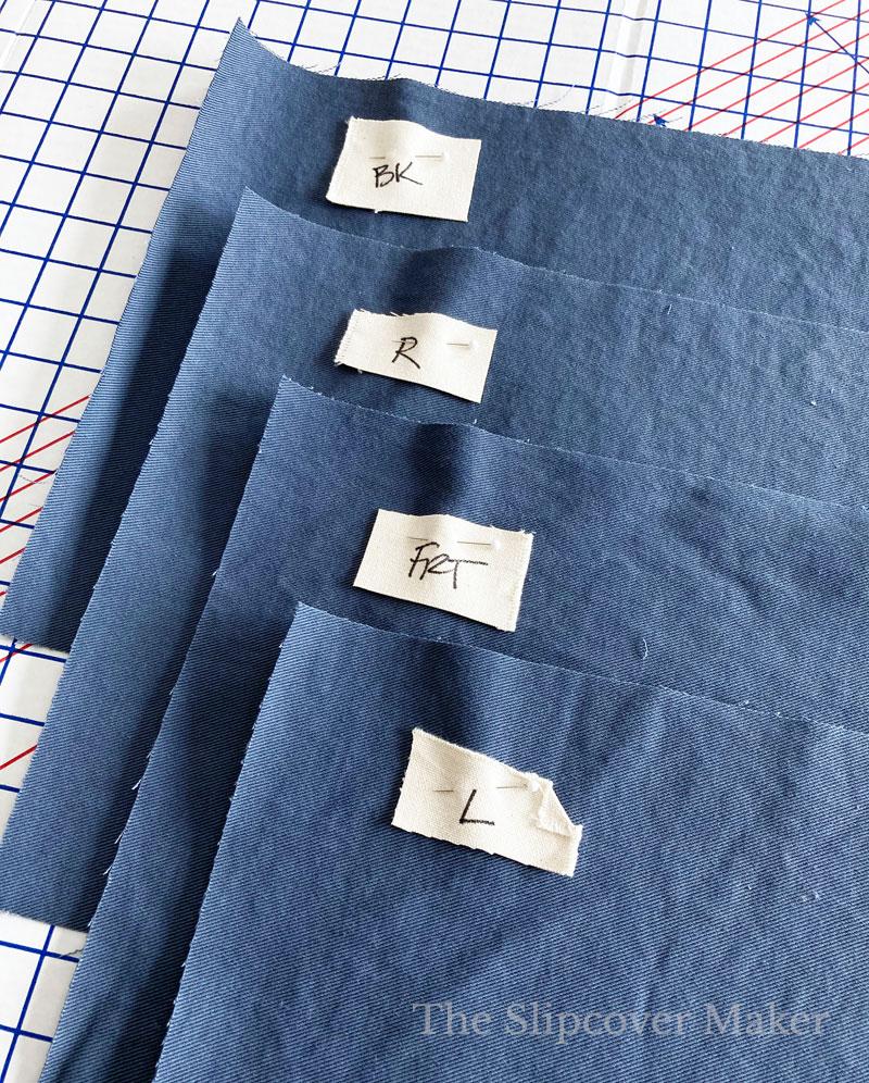 Blue denim slipcover skirt panels cut and stacked.