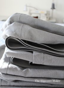 Folded and stacked grey canvas cushion covers.