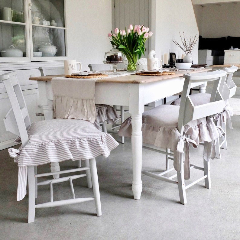 Dining chairs with ruffled seat covers.