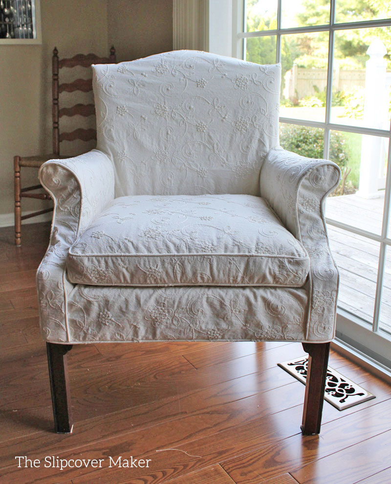 Dining chair with ivory embroidered slipcover.