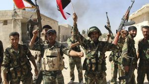 FILE - In this file photo taken on Sunday, Oct. 11, 2015, Syrian soldiers waving Syrian flags celebrate the capture of Achan, Hama province, Syria. The ever-growing, secret defense budgets and poor oversight of militaries in the Middle East make them susceptible to corruption and more vulnerable to extremist violence, a watchdog group warned. (Alexander Kots/Komsomolskaya Pravda via AP, File)