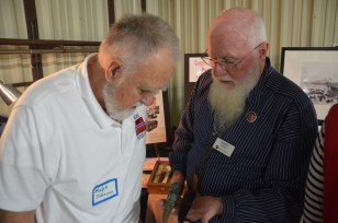 Perry Straw (right) shows off his knives to Ralph (Ole) Johnson.
