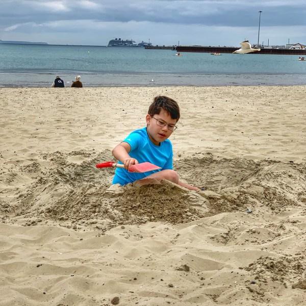 A boy building sandcastles on a beach