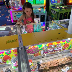 A girl playing the 2p machines at an amusement arcade