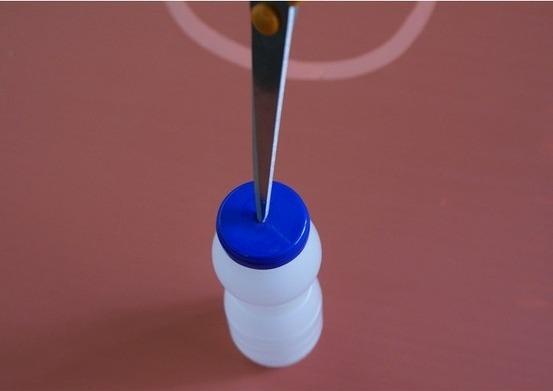 Haz un agujero en la tapa de la botella.