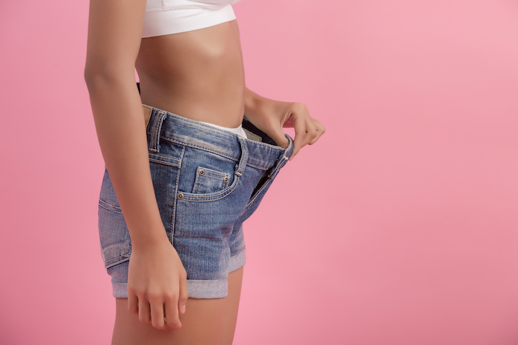 Diet concept and weight loss. Woman in oversize jeans