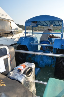 Suitcases and people loaded on the tractor. Ready to go on land. Phi Phi. Photo: ©Slowaholic