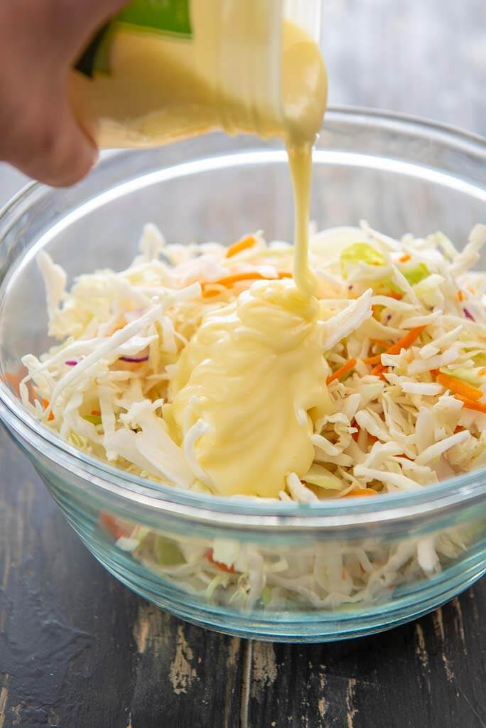 pouring dressing onto coleslaw in a glass bowl