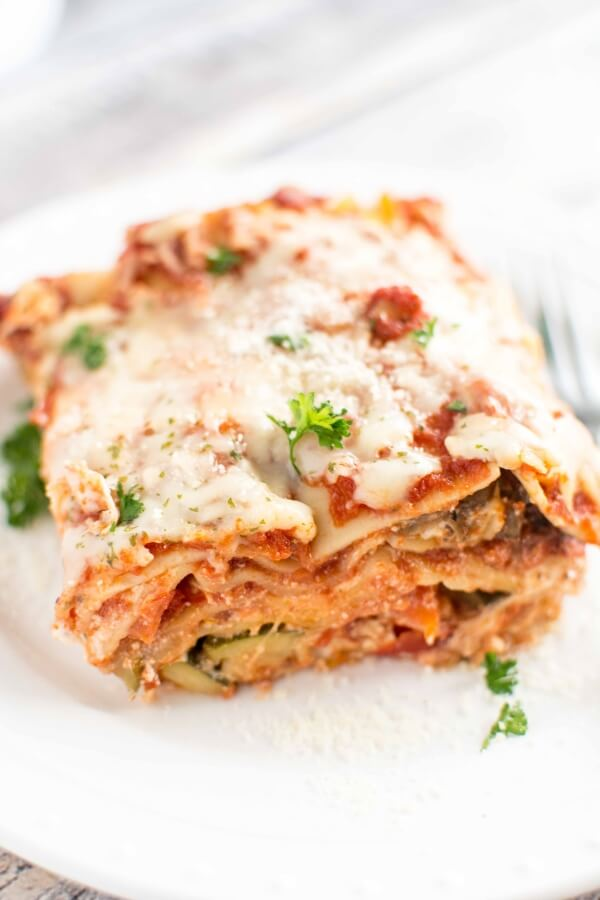 Slow Cooker Veggie Lasagna served on a white plate with a fork resting on the side.
