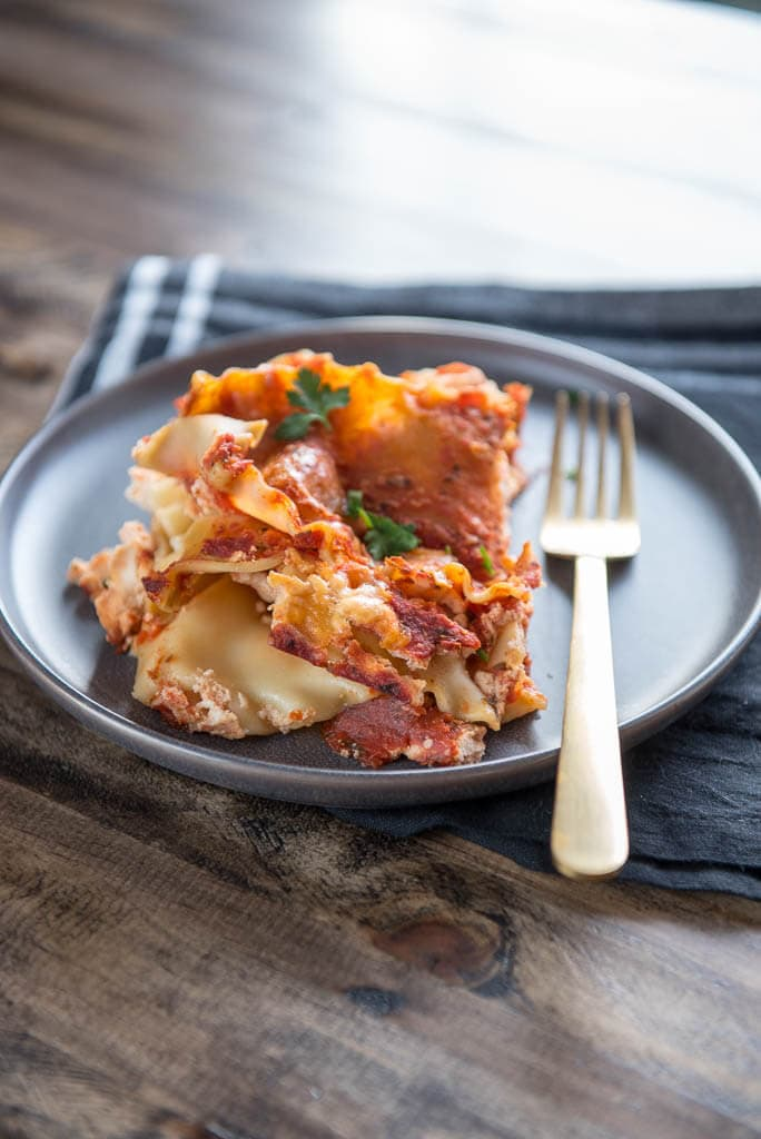 3 Ingredient Slow Cooker Lasagna on gray plate with gold fork and black napkin on wood table