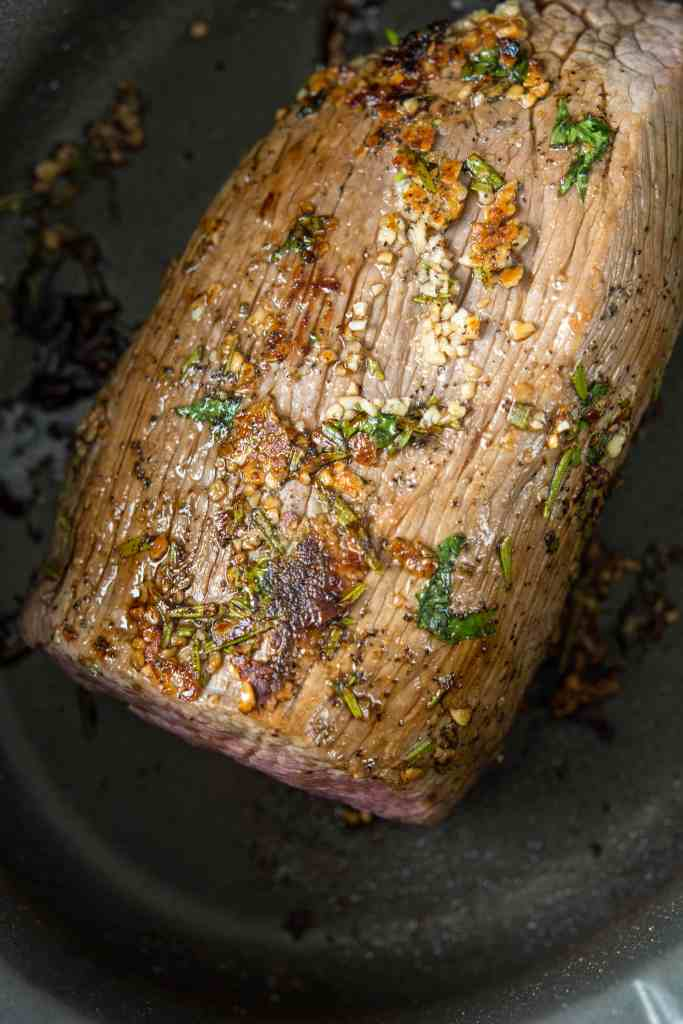 Seared Slow Cooker Roast Beef in multi-cooker covered in oil, rosemary, garlic, salt and pepper.