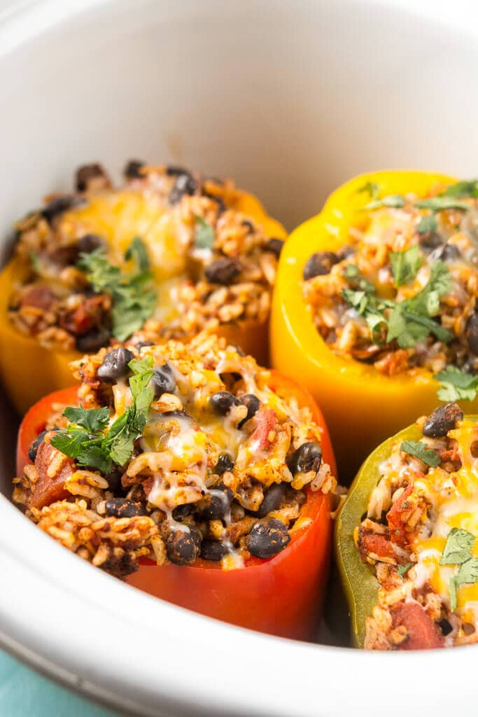 Close up picture of slow cooker stuffed peppers topped with cilantro in white crock.