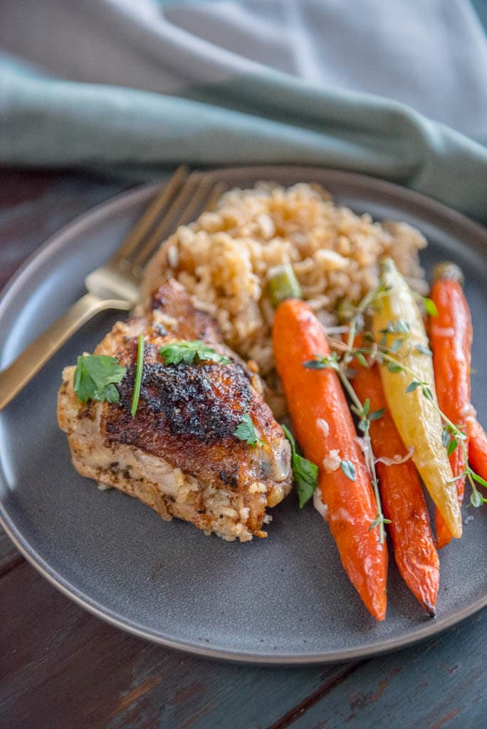 Slow Cooker Baked Chicken Thighs with rice on gray plate with gray napkin and carrots