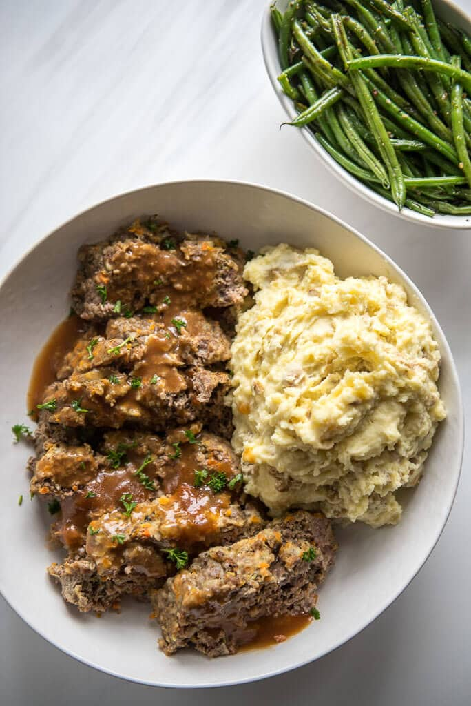 White platter of Slow Cooker Meatloaf with a heaping side of Buttermilk Mashed Potatoes. Crispy Garlic Onion Green Beans served on the side.