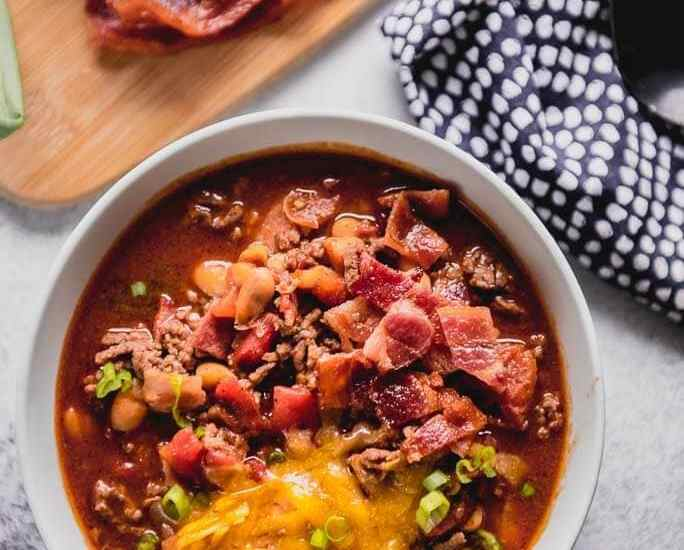 slow cooker maple bacon chili topped with cheese and green onions