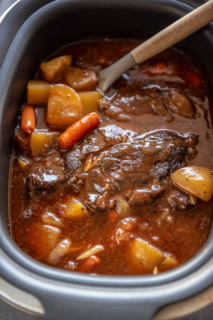 looking down into slow cooker full of pot roast, carrots, potatoes and gravy