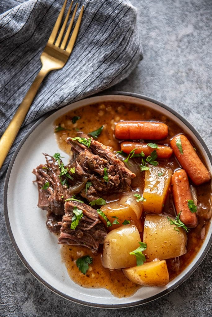 white plate with serving of pot roast, carrots, potatoes and gravy topped with parsley