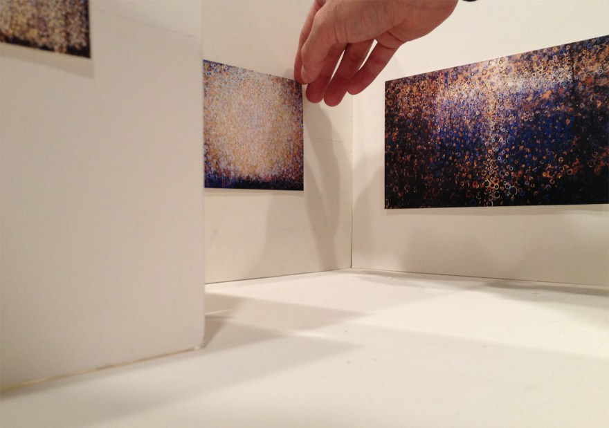 Hand reaches into doll-house-sized model of art gallery to adjust miniature painting hanging on wall