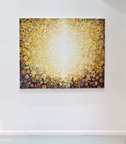 "Yellow and white patterns of circles glow from the painting ""rajah"" by Randall stoltzfus, shown here in a gallery install in New York, NY"