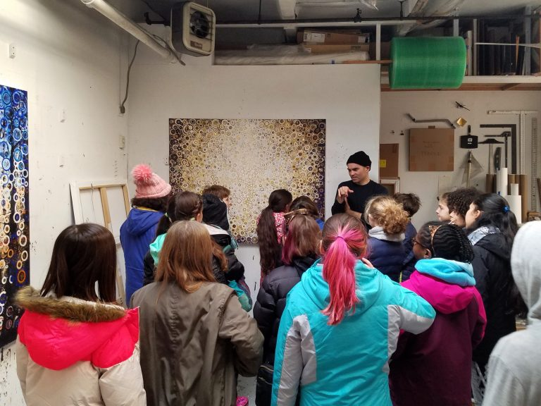 A 6th grade class gathers around Randall Stoltzfus in his studio