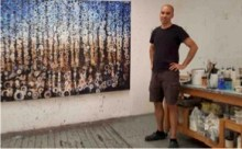 Randy Stoltzfus stands with one of his paintings in his Brooklyn studio