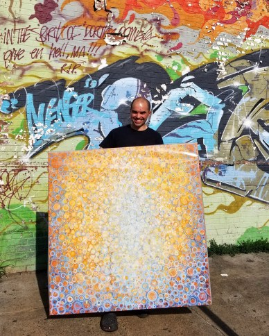 "All wrapped up and ready to go! Randall Stoltzfus holds his painting ""Seek"" in front of the graffiti covered wall outside his Brooklyn studio"