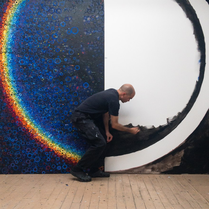 Randall Stoltzfus beginning work on the second half of a n 8 by 10 foot rainbow colored canvas