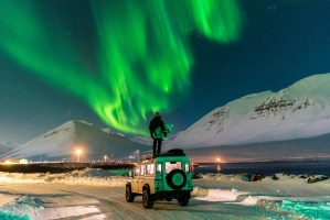 A surfer on top of a car under the Northern light
