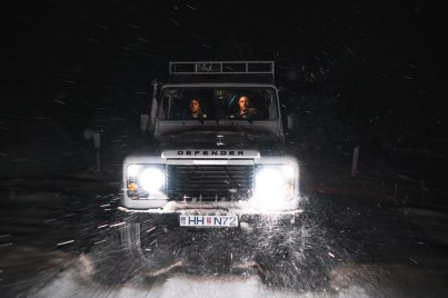 people in a defender during a snow storm