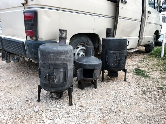 hand crafted iron stove in front of a van