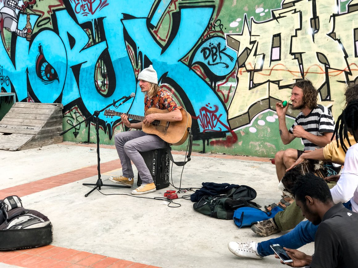 guy playing guitar in front of a graffiti