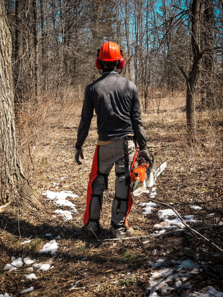 a guy holding a chainsaw in the woods