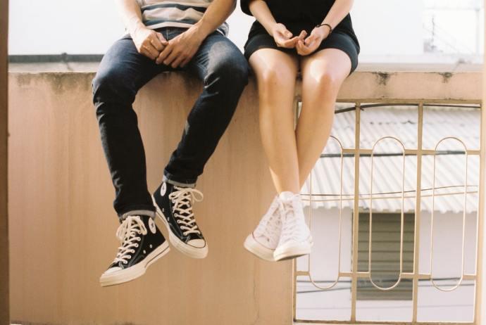 To nie jest świat dla kobiet. To nie jest świat dla mężczyzn. na obrazku kobieta i mężczyzna siedzący na murku, pokazani od pasa w dół. Oboje mają na nogach trampki.