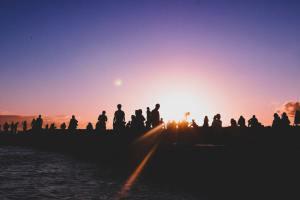 Jeszcze będzie normalnie. Na zdjęciu tłum ludzi o zachodzie słońca nad wodą.