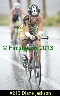 Photo of 2013 Ironman 70.3 World Championship competitor Diane Jackson brightly smiling despite the rain and wet roads while the bike.