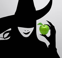 witch in silhouette holding a green apple