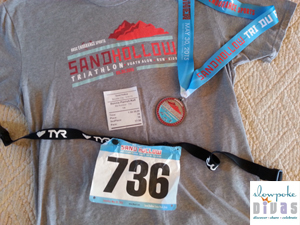 Color photo of Sand Hollow Triathlon, Duathlon, 10K & 5K men's race shirt, finisher medal, race bib, and timing results ticket.