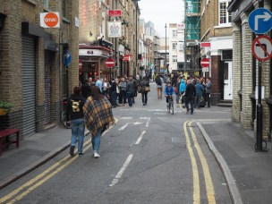 The streets in London's Shoreditch neighbourhood are taken over by people. This is only possible by the fine grain retail and higher density that makes driving through quickly difficult.