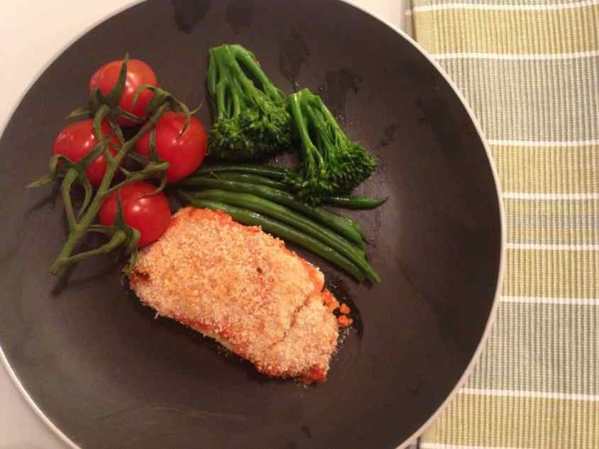 baked cod with red pesto served on a black plate