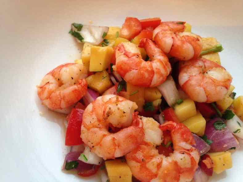 mango salsa with prawns on top served on a white plate
